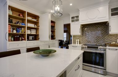 classic kitchen, white cabinets, glass pendants, caesarstone counters, .wine cellar, mosaic backsplash