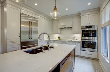 classic kitchen, white cabinets, walnut cabinets, glass pendants, caesarstone counters, island