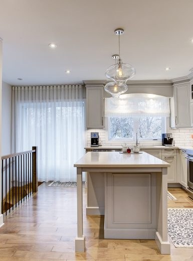 classic kitchen, white cabinets, walnut cabinets, glass pendants, caesarstone counters, island. stools, mosaic backsplash